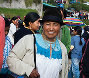 A woman with felt hat and gold necklaces attends Otavalo Market in Ecuador, Imbabura Province, South America. The culturally vibrant town of Otavalo attracts many tourists to a valley of the Imbabura Province of Ecuador, surrounded by the peaks of Imbabura 4,610m, Cotacachi 4,995m, and Mojanda volcanoes. The indigenous Otavaleños are famous for weaving textiles, usually made of wool, which are sold at the famous Saturday market and smaller markets during the rest of the week. The Plaza del Ponchos and many shops tantalize buyers with a wide array of handicrafts. Nearby villages and towns are also famous for particular crafts: Cotacachi, the center of Ecuador's leather industry, is known for its polished calf skins; and San Antonio specializes in wood carving of statues, picture frames and furniture. Otavaliña women traditionally wear distinctive white embroidered blouses, with flared lace sleeves, and black or dark over skirts, with cream or white under skirts. Long hair is tied back with a 3cm band of woven multi colored material, often matching the band which is wound several times around their waists. They usually have many strings of gold beads around their necks, and matching tightly wound long strings of coral beads around each wrist. Men wear white trousers, and dark blue ponchos. Otavalo is also known for its Inca-influenced traditional music (sometimes known as Andean New Age) and musicians who travel around the world.