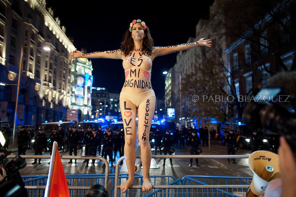 Jill Love stands topless on the police fence with body painting messages while riot policemen stand behind guarding the congress at Neptuno Square on December 14, 2013 in Madrid, Spain. Social movements groups called a 'Rodea el Congreso' 'Surrounding the Parliament' protest in reaction to the financial and social cuts, but also a new law the Spanish government is working that aims to set heavy fines. Around 1,500 policemen were on duty to protect the congress. The bill will set up fines of up to 30,000 euros for offenses related to social movements protests, insulting the state or offending or filming the authorities. After the demonstration some protesters clashed with riot policemen