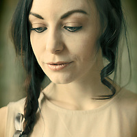 Young Woman with long dark hair in plait in thoughtful pose