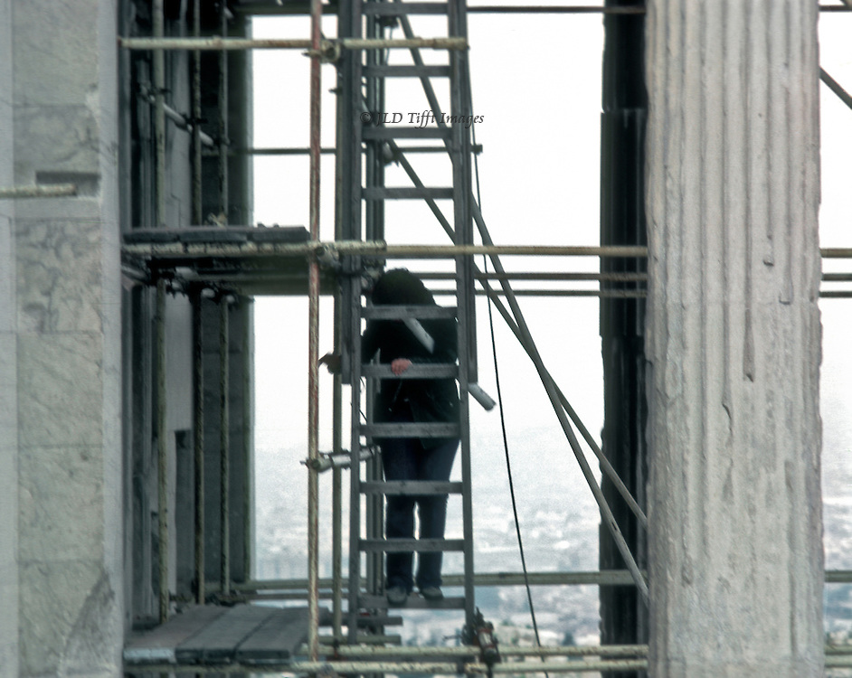 Telephoto view of a supervisor on a ladder between two Ionic columns of the Erechtheum points toward someone or something below on the left. City of Athens spreads out in the distance.