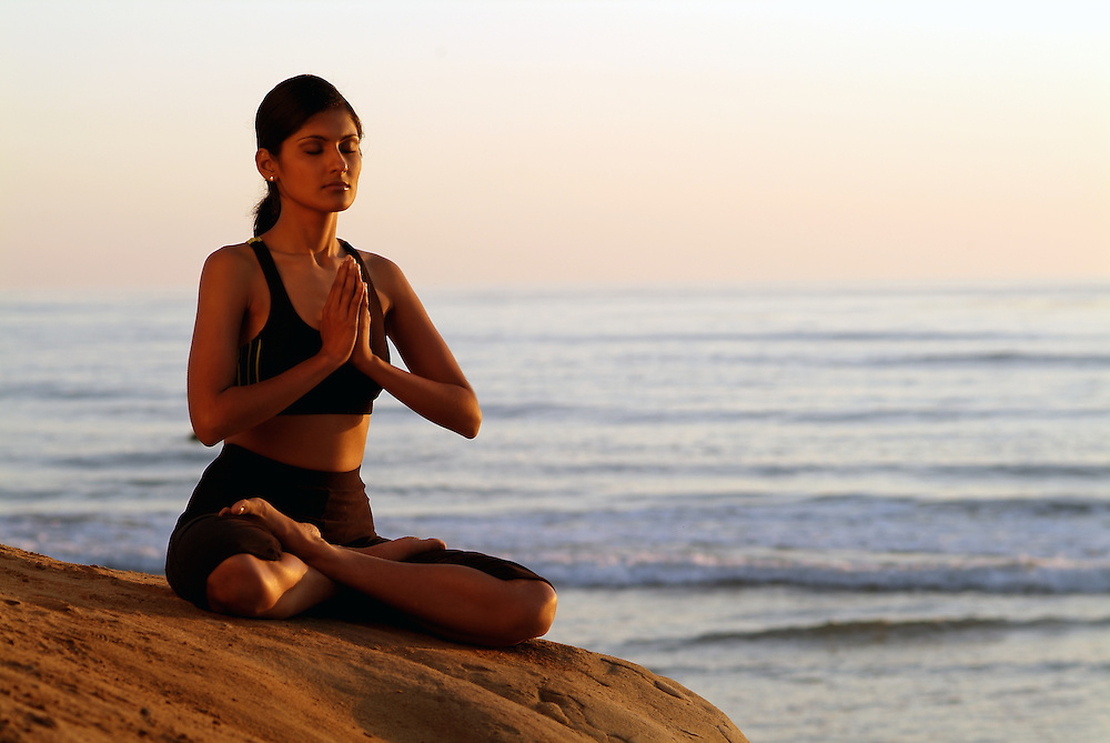 Indian girl meditating on cliffs above Pacific Ocean.