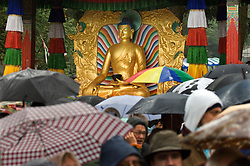 "HUY, BELGIUM - MAY-29-2006 - The faithful prepare themselves and wait in the pouring rain to see the Dalai Lama during an inauguration ceremony for a new temple at the Institute Yeunten Ling in Huy, Belgium. The new temple was named Thubten Sherab Ling by the Dalai Lama, which means ""The garden of study and practice of the teachings of the Enlightened One"".  This marks the start of the Dalai Lama's five-day visit to Belgium where he will speak in both Brussels and Antwerp. (PHOTO © JOCK FISTICK)"