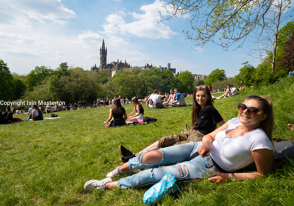 Glasgow, Scotland, UK. 15 May 2019. Warm sunny weather in the city brought hundreds of young sun-seekers to Kelvingrove Park in the city's West End. Pictured ; Holly, left, a student at Glasgow School of Art and Naomi from Leeds enjoy the warm sunny weather.
