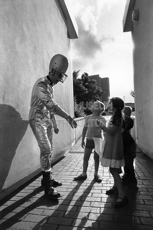 Jerry Dammers of 2Tone group, The Specials, entertaining a group of young children, dressed as an alien, UK, 1980's.