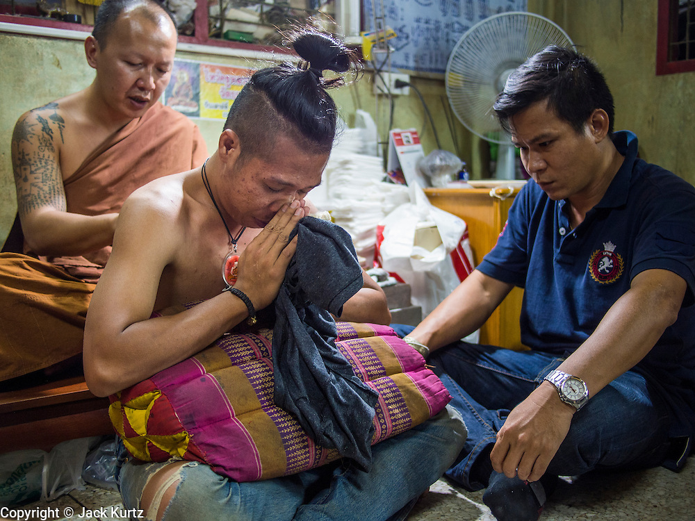 """14 MARCH 2014 - NAKHON CHAI SI, NAKHON PATHOM, THAILAND: A Buddhist monk gives a man a sak tant tattoo at Wat Bang Phra. Wat Bang Phra is the best known """"Sak Yant"""" tattoo temple in Thailand. It's located in Nakhon Pathom province, about 40 miles from Bangkok. The tattoos are given with hollow stainless steel needles and are thought to possess magical powers of protection. The tattoos, which are given by Buddhist monks, are popular with soldiers, policeman and gangsters, people who generally live in harm's way. The tattoo must be activated to remain powerful and the annual Wai Khru Ceremony (tattoo festival) at the temple draws thousands of devotees who come to the temple to activate or renew the tattoos. People go into trance like states and then assume the personality of their tattoo, so people with tiger tattoos assume the personality of a tiger, people with monkey tattoos take on the personality of a monkey and so on. In recent years the tattoo festival has become popular with tourists who make the trip to Nakorn Pathom province to see a side of """"exotic"""" Thailand.   PHOTO BY JACK KURTZ"""