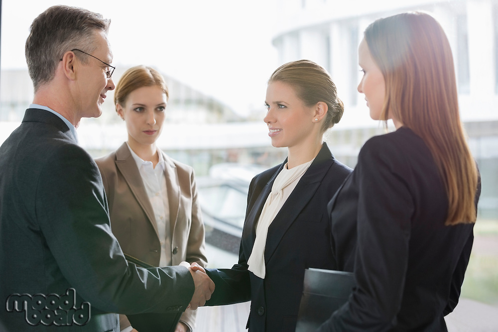 Confident business people shaking hands at workplace