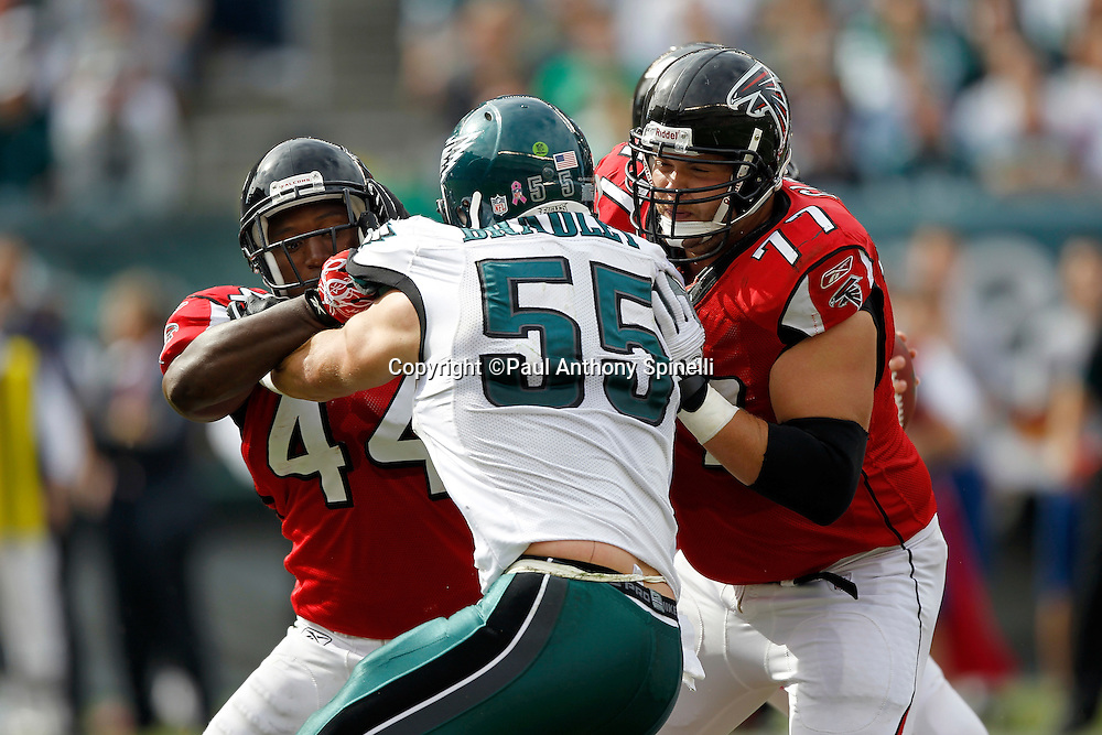 Philadelphia Eagles linebacker Stewart Bradley (55) gets double team blocked by Atlanta Falcons running back Jason Snelling (44) and Falcons offensive tackle Tyson Clabo (77) during the NFL week 6 football game against the Atlanta Falcons on Sunday, October 17, 2010 in Philadelphia, Pennsylvania. The Eagles won the game 31-17. (©Paul Anthony Spinelli)