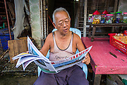 17 JUNE 2013 - YANGON, MYANMAR: A man reads a Burmese newspaper in a market in Yangon. The Burmese newspaper industry has enjoyed explosive growth this year after private ownership was allowed in 2013. Private newspapers were shut down under former Burmese leader Ne Win in the early 1960s. The revitalized private press is a sign of the dramatic changes sweeping Myanmar, formerly Burma, in the last three years.      PHOTO BY JACK KURTZ