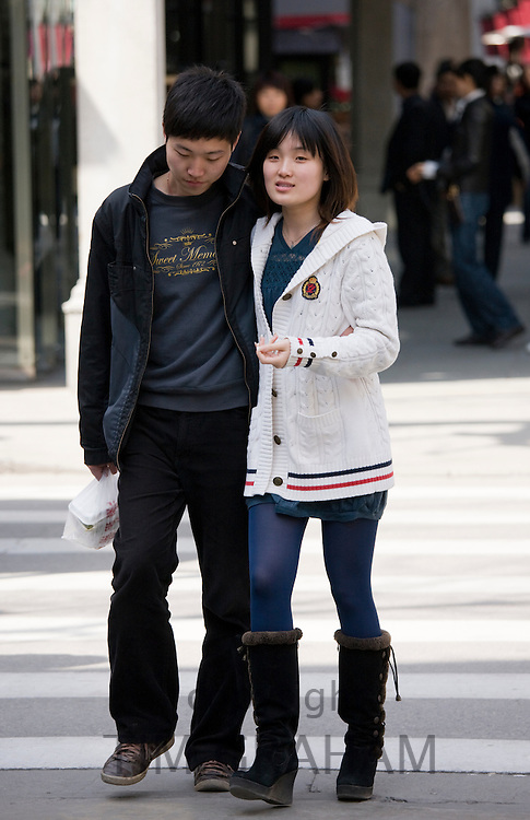 Couple walking in redeveloped Xintiandi area, Huang Pi Road, Shanghai, China