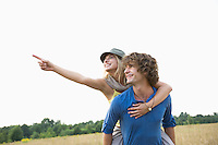Happy woman showing something while enjoying piggyback ride on man in field