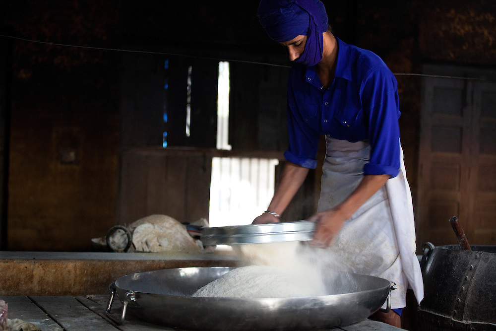 A young Nihang Sikh cooks at an ancient Sikh kitchen. The Nihangs are warrior sikhs and their attire consists of blue color.