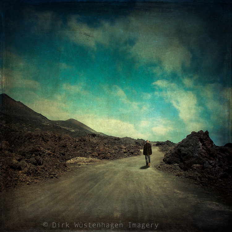 Man walking on a road through a desolate landscape - manipulated photograph