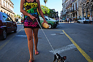 Cuban woman walking the dog in the mornin, before the temperature rises