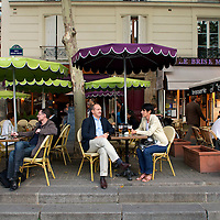 People at outdoor cafes on the Place Stravinsky.