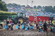The cleaning/recycle team move in to sort out the mess outside the Beat Hotel, despite the festival motto, Leave no Trace - The 2016 Glastonbury Festival, Worthy Farm, Glastonbury.