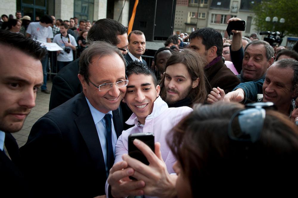 François Hollande, kanidaat van de Partie Socialiste bij de Franse  Presidentsverkiezingen poseert geduldig voor Iphone foto's met potentiële kiezers. Meeting in Blois.