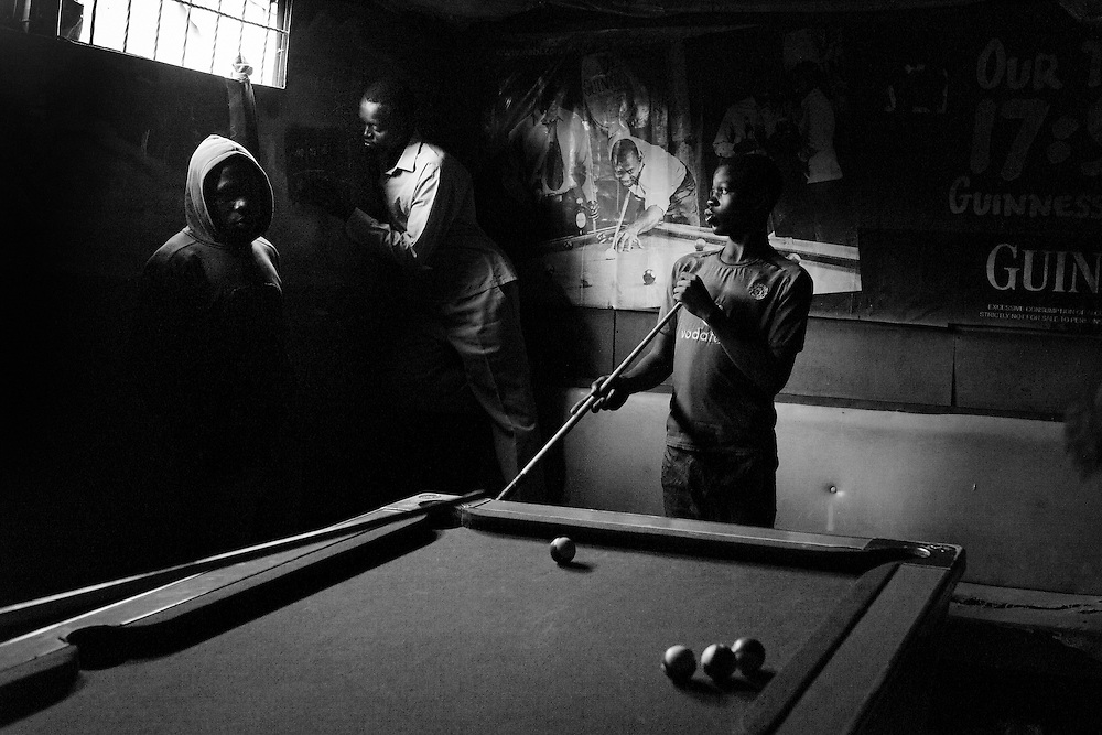 "NAIROBI, KENYA - AUGUST 18, 2011: Idle youth in Kisumundogo village play ""Whiteless,"" a popular billiards game in Kenya, at the former Railbreeze Pub. Once an active bar and restaurant, Railbreeze is now an empty hut in which Kenyan youth play pool to pass the time. <br />