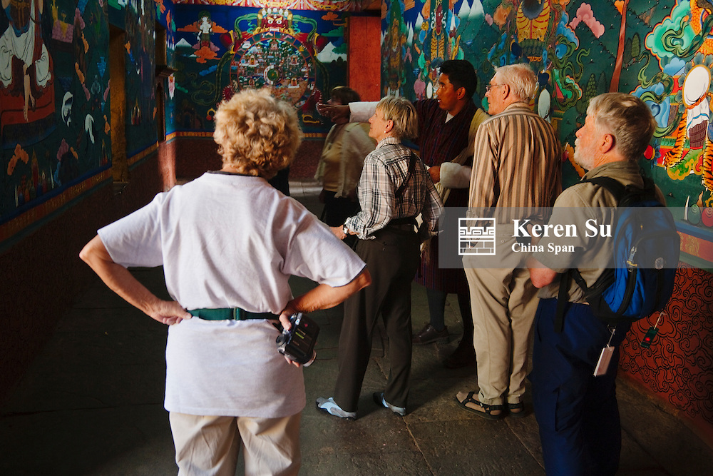 Western traveler look at murals in Paro Dzong, Paro, Bhutan