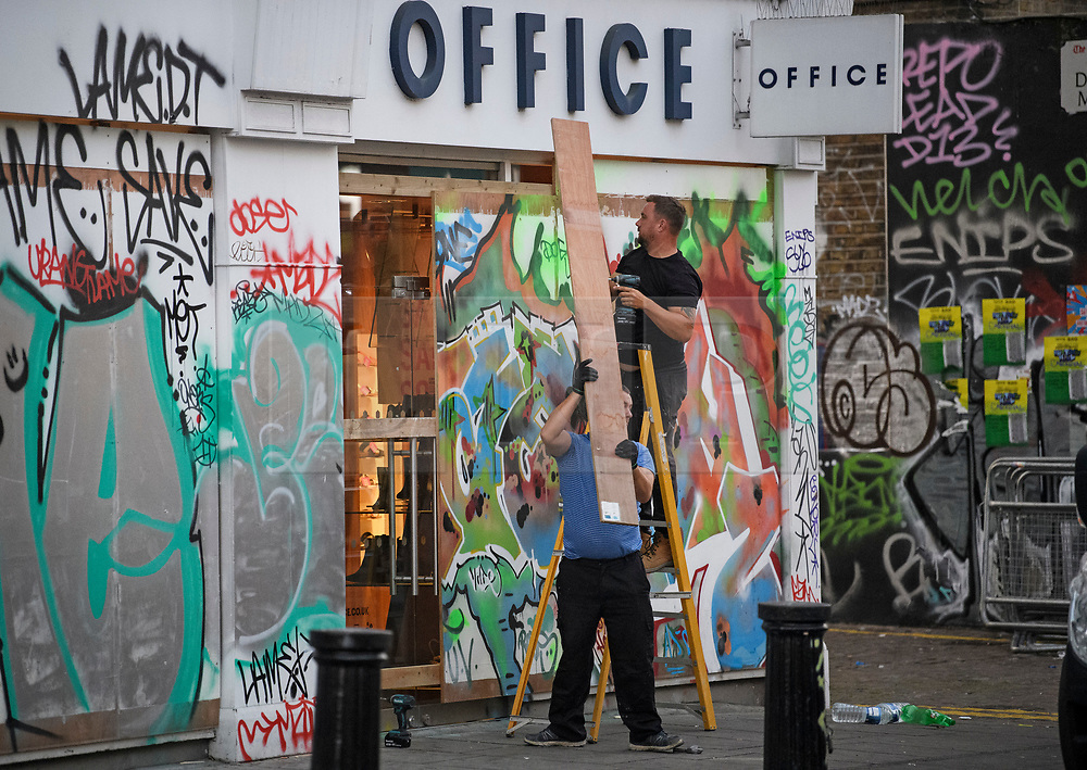 © Licensed to London News Pictures. 27/08/2019. London, UK. Boards being taken down from retail property in Notting Hill, west London, in the aftermath of the 2019 Notting Hill carnival. The two day event is the second largest street festival in the world after the Rio Carnival in Brazil, attracting over 1 million people to the streets of West London. Photo credit: Ben Cawthra/LNP