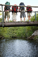Four teenagers (16-17 years) standing on bridge carrying backpacks looking down back view