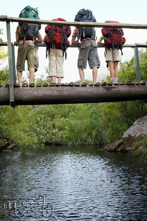 Four teenagers (16-17 years) standing on bridge carrying backpacks looking down back view