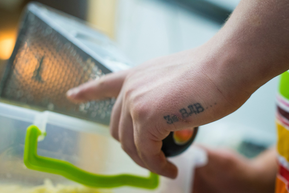 "A tattoo is visible on the hand of Artyom Rudenko, a veteran of Ukraine's Airborne forces, as he grates cheese at Veterano Pizza on January 23, 2016 in Kiev, Ukraine. The tattoo, an acronym, means ""For the Airborne."" (Pete Kiehart for The New York Times)"
