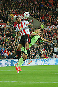 Sunderland defender Patrick Van Aanholt beats Manchester City forward Sergio Aguero to the header during the Capital One Cup match between Sunderland and Manchester City at the Stadium Of Light, Sunderland, England on 22 September 2015. Photo by Simon Davies.