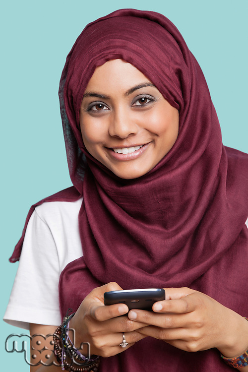 Portrait of happy young Muslim woman using cell phone against blue background