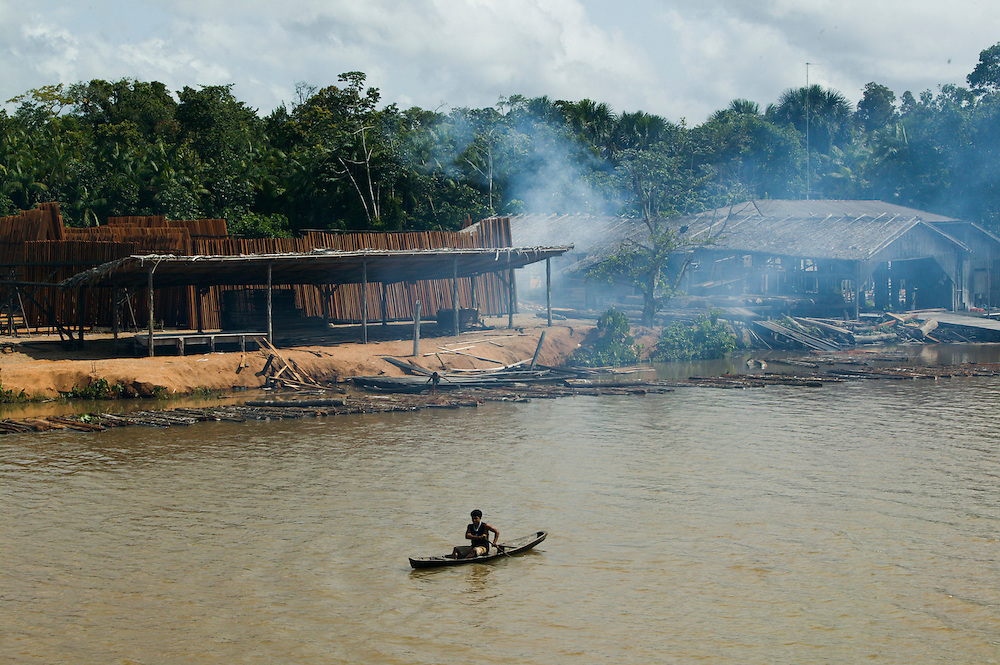 Dec. 11, 2003. A man in a canoe passes a sawmill near Breves in Para State, Brazil. ©Daniel Beltra