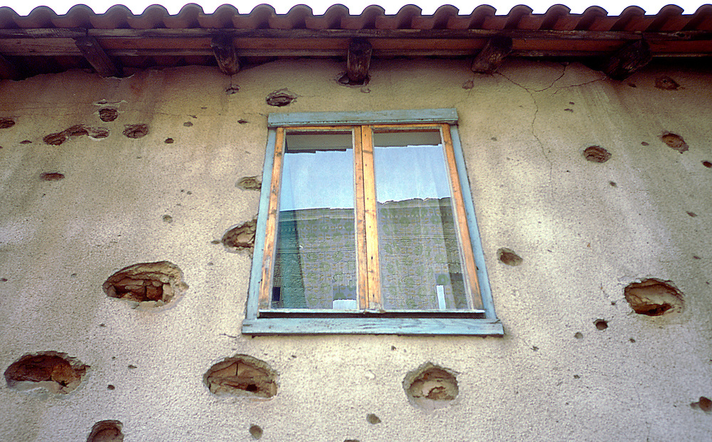 New window in Sarajevo house, riddled with bullet indentations and holes, after the war