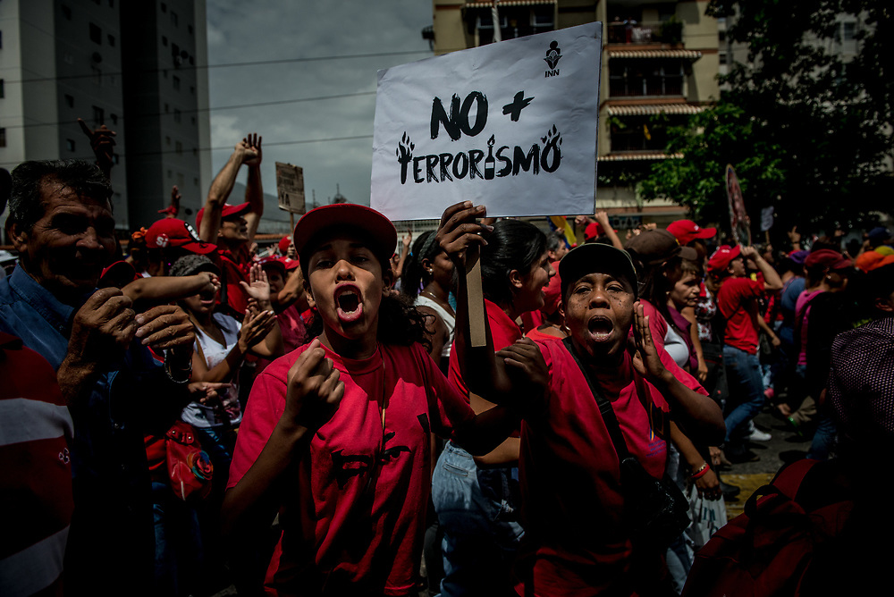 """CARACAS, VENEZUELA - APRIL 19, 2017:  Socialist government supporters shout at opposition protesters, while holding  a sign that says, """"No more Terrorism"""" as their two marches crossed paths on the same street in """"La Vega"""" slum. Government supporters also held a march today.  Hundreds of protesters showed up in La Vega slum, many more than were present supporting the opposition.  Several people present said they were obligated by the government to attend in order to keep their jobs and access to government subsidized food and housing.  PHOTO: Meridith Kohut"""