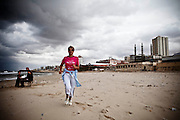 A woman enjoys a run along the seafront, a practice she steadfastly insists on enjoying, despite the stares of surprised fishermen and male beachgoers [Tanya Habjouqa]