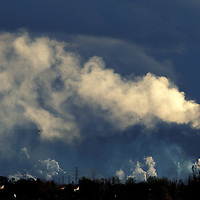Canada, Ontario, Setting sun lights plumes of smoke and steam from huge paper mill in Thunder Bay along Lake Superior