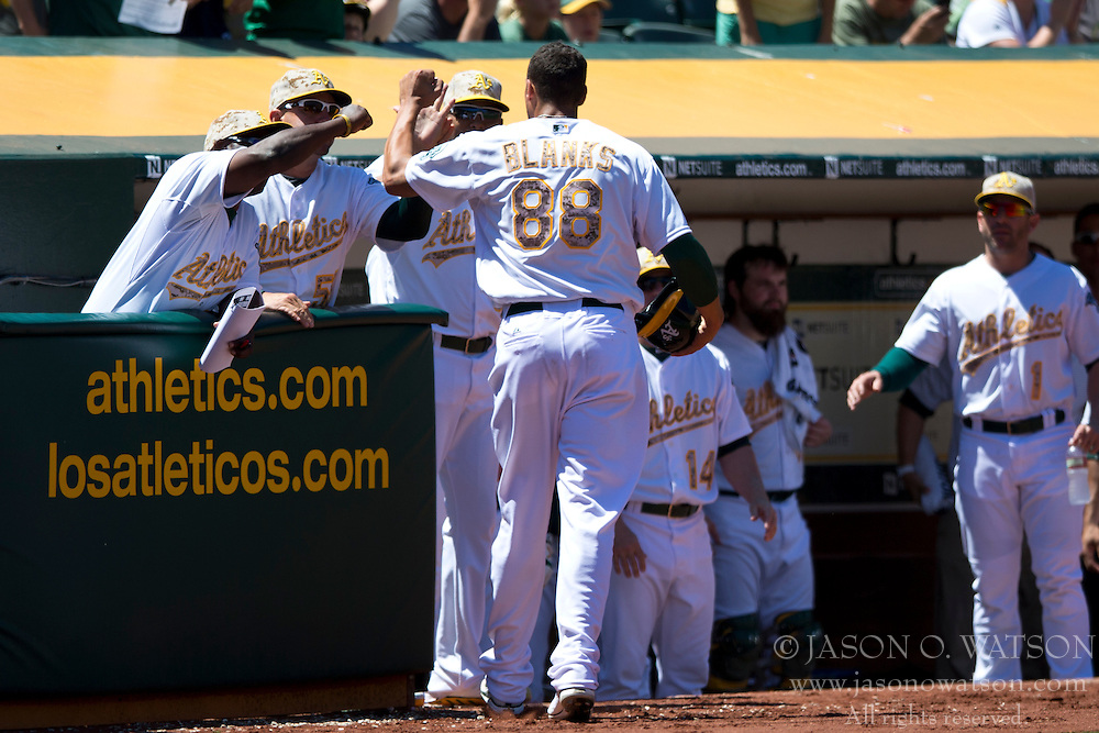 OAKLAND, CA - MAY 26:  Kyle Blanks #88 of the Oakland Athletics is congratulated by teammates after scoring a run against the Detroit Tigers during the fourth inning at O.co Coliseum on May 26, 2014 in Oakland, California. The Oakland Athletics defeated the Detroit Tigers 10-0.  (Photo by Jason O. Watson/Getty Images) *** Local Caption *** Kyle Blanks