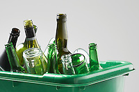 Empty bottles in green container close-up