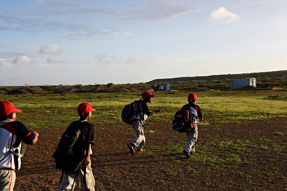 "WILLEMSTAD, CURACAO - DECEMBER 10, 2014:  Members of the newly formed Akademia de Beisbol Bandabou Tigers, coached by Didi Gregorius' father Johannes ""Didi"" Gregorius, head home after practice. That hardscrabble, rock-filled ground they're walking through is the infield, which has been attributed to the success of many fine shortstops coming out of Curacao, who learned how to field on that surface. (photo by Melissa Lyttle)"