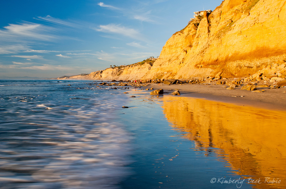 Golden sunlight reflecting from the cliffs north of Scripps Pier in La Jolla, California, looking towards Blacks Beach and Torrey Pines State Natural Reserve.