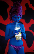 A woman painted blue drinks alcoholic mix, Ibiza, 2000s.