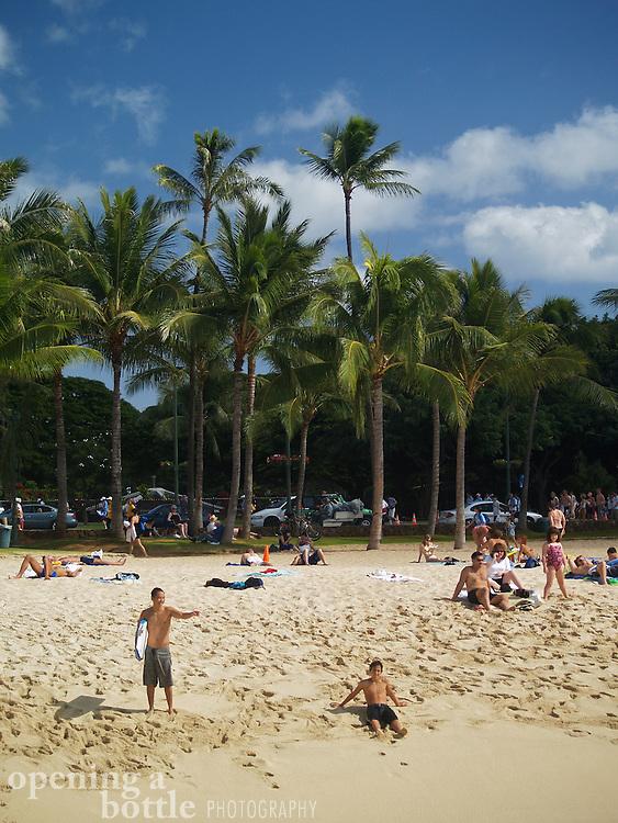 Teenage boys and tourists hanging out on Waikiki Beach (Oahu), Hawaii.