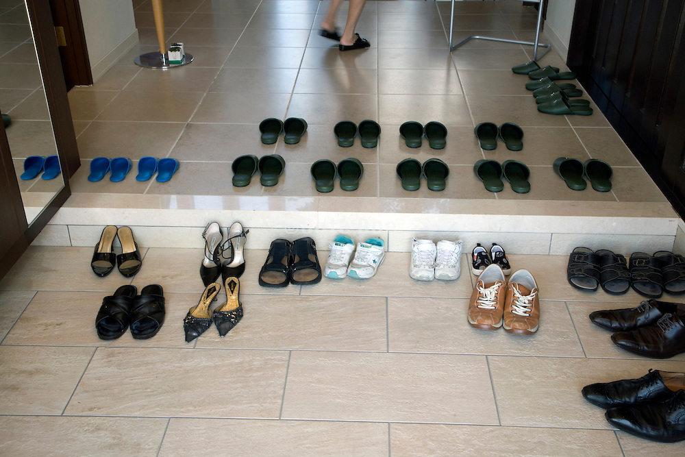 rows of slippers and shoes at the entrance of a house