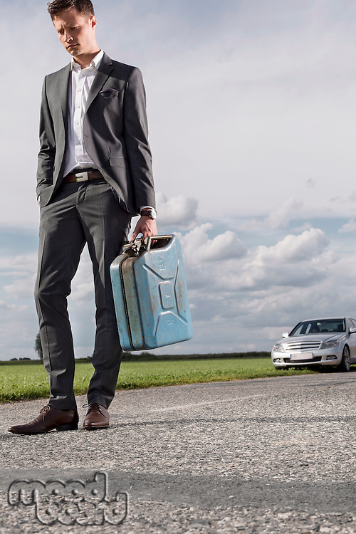 Full length of sad young businessman carrying petrol can with broken car in background at countryside