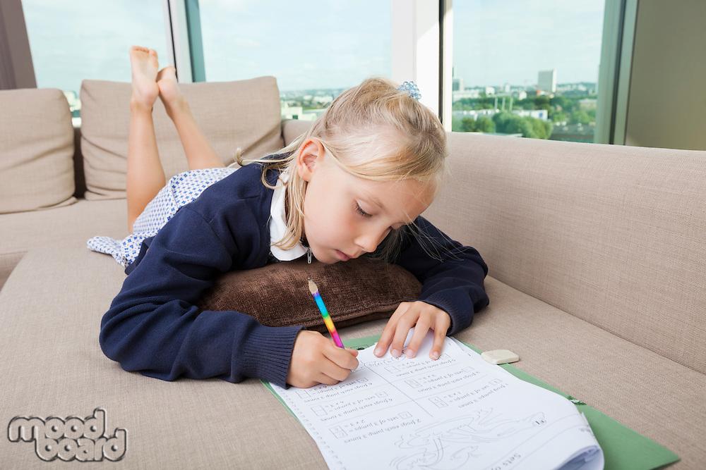 Little girl doing mathematics homework on sofa