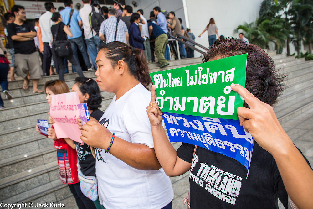 """23 JANUARY 2013 - BANGKOK, THAILAND:  Supporters of convicted magazine editor Somyot Prueksakasemsuk picket the front of Bangkok Criminal Court after Somyot's sentencing. Somyot was sentenced to 11 years imprisonment on """"Lese Majeste"""" charges Wednesday. He was arrested on April 30, 2011, and charged under article 112 of Thailand's penal code, which states that ?whoever defames, insults or threatens the King, the Queen, the Heir-apparent or the Regent, shall be punished with imprisonment of three to fifteen years"""" after the magazine he edited, """"Red Power"""" (later changed to """"The Voice of Thaksin"""") published two articles by Jit Pollachan, the pseudonym of Jakrapob Penkair, the exiled former spokesman of exiled fugitive former Prime Minister Thaksin Shinawatra. Jakrapob, now living in Cambodia, has never been charged with any crime for what he wrote.      PHOTO BY JACK KURTZ"""