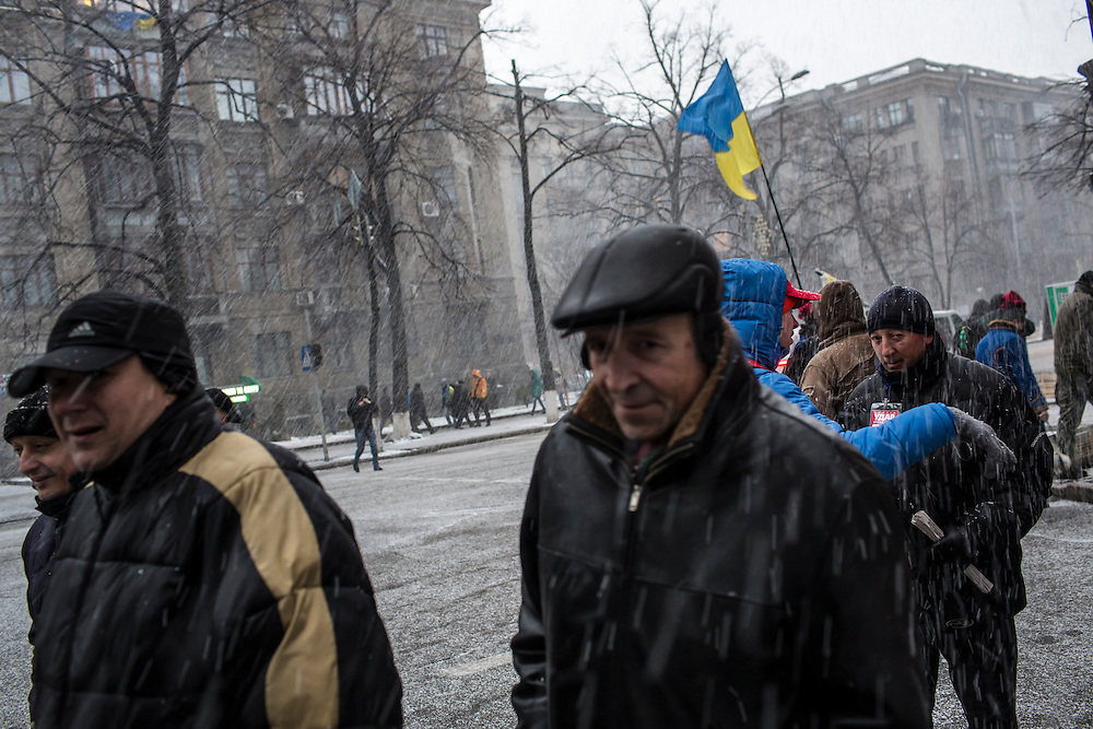 KIEV, UKRAINE - DECEMBER 6: Anti-government protesters and pedestrians walk through a sudden snow shower on December 6, 2013 in Kiev, Ukraine. Thousands of people have been protesting against the government since a decision by Ukrainian president Viktor Yanukovych to suspend a trade and partnership agreement with the European Union in favor of incentives from Russia. (Photo by Brendan Hoffman/Getty Images) *** Local Caption ***