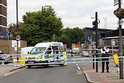 © Licensed to London News Pictures. 08/08/2017. LONDON, UK.  Police at the crime scene cordon on the corner of Old Kent Road and Ilderton Road, next to the Afrikiko Bar Restaurant and Club. Police were called at around 2am and found a 19 year old man with stab injuries, who was pronounced dead about an hour later. Five people have now been arrested in connection with stabbing and are being held at a south London police station.  Photo credit: Vickie Flores/LNP