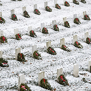 Headstones at Arlington National Cemetery in the snow. Volunteers have added a holiday wreath to each gravesite. Arlington, Virginia, United States.