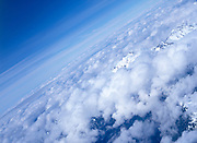 Cumulus clouds sitting over mountain peaks