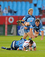 PRETORIA, South Africa, 14 May 2011. Luke Rooney of the Melbourne Rebels is tackled by Stephan Dippenaar and a flying Deon Stegmann of the Bulls during the Super15 Rugby match between the Bulls and the Melbourne Rebels at Loftus Versfeld in Pretoria, South Africa on 14 May 2011..Photographer : Anton de Villiers / SPORTZPICS
