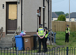 Pictured: police stand guard outside the house in Mayfield, Armadale this morning where windows were broken and a car was set alight as an angry crowd of locals jostled with a heavy police presence on Tuesday night after allegations against a resident.<br /> <br /> &copy; Dave Johnston / EEm