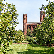 Smithsonian Castle from Moongate Garden. Formally known as the Smithsonian Institution Building, the Smithsonian Castle houses the administrative headquarters fo the Smithsonian Institution as well as some a permanent exhibition titled Smithsonian Institution: America's Treasure Chest. It's distinctive architectural style stands out on the southern side of the National Mall in Washington DC.